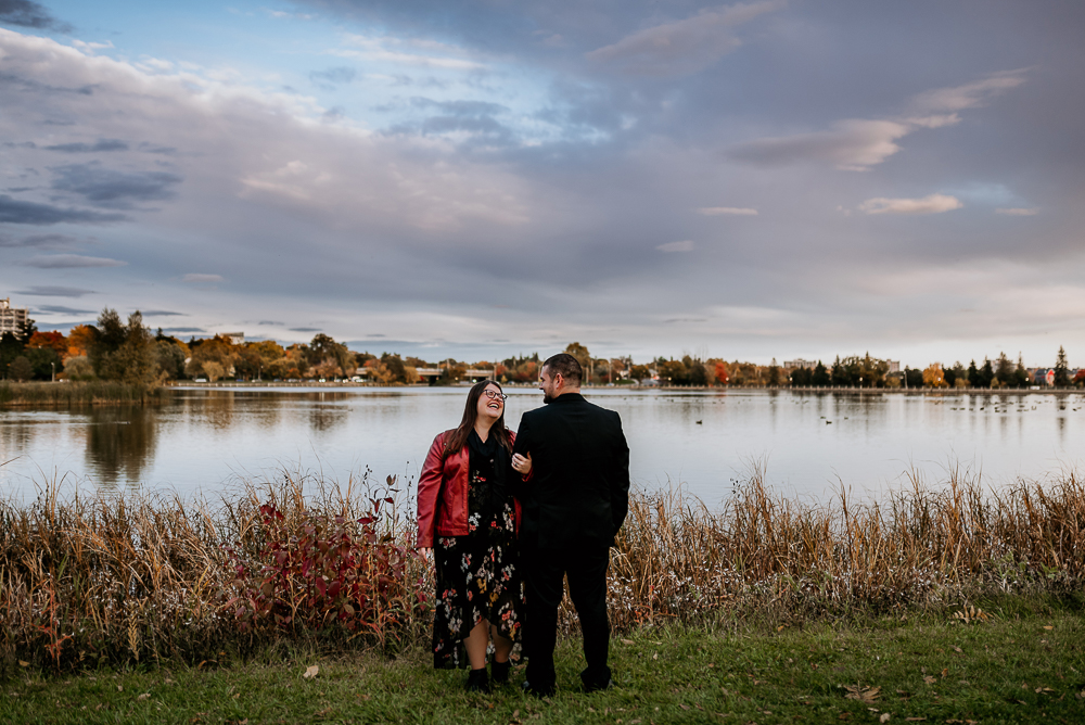 Couple standing side by side, arm linked together as the soon to be bride looks up at her fiancé and laughs. Carleton University is seen in the background beyond Dow's Lake. Ottawa wedding photographer Samantha Danis.