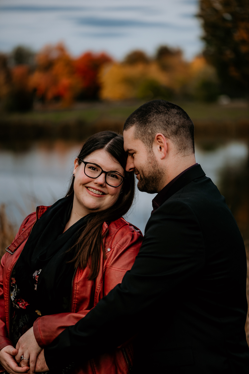 Engaged couple cuddling during their engagement session. Fianc. is leaning his head into his bride as she looks into the camera, smiling. Beautiful fall colours displayed int he trees int he background beyond Dow's Lake.