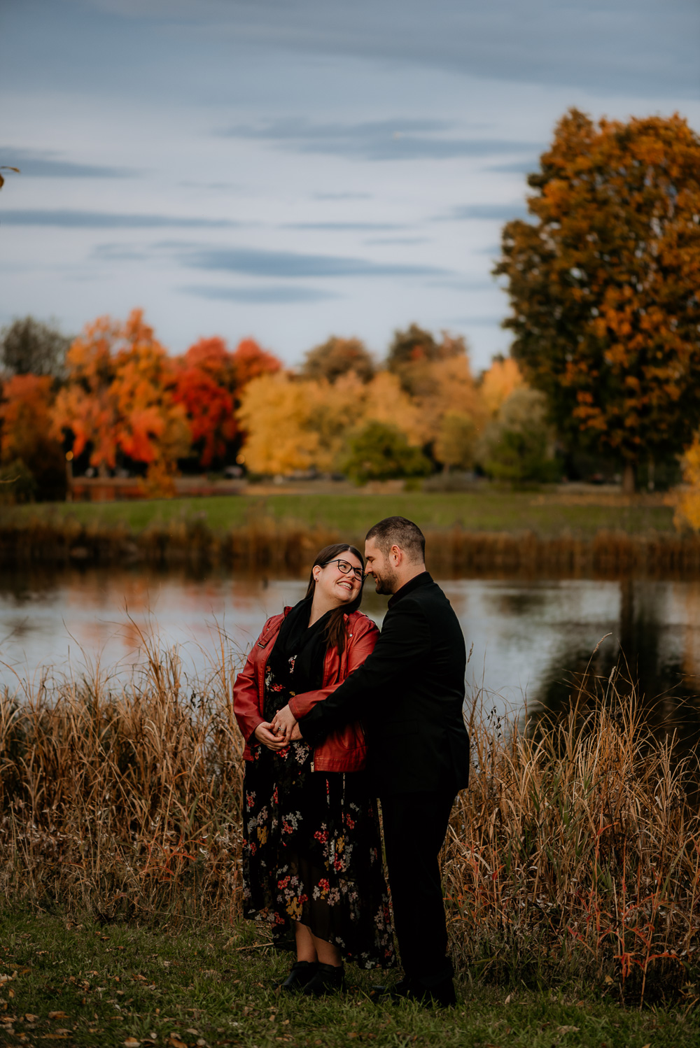 Crisp fall engagement session at Dow's lake. Couple standing with the bride having her back to the groom as they look over at each other lovingly. Beautiful fall colours in the trees surrounding them. Photo taken by Samantha Danis Photography.