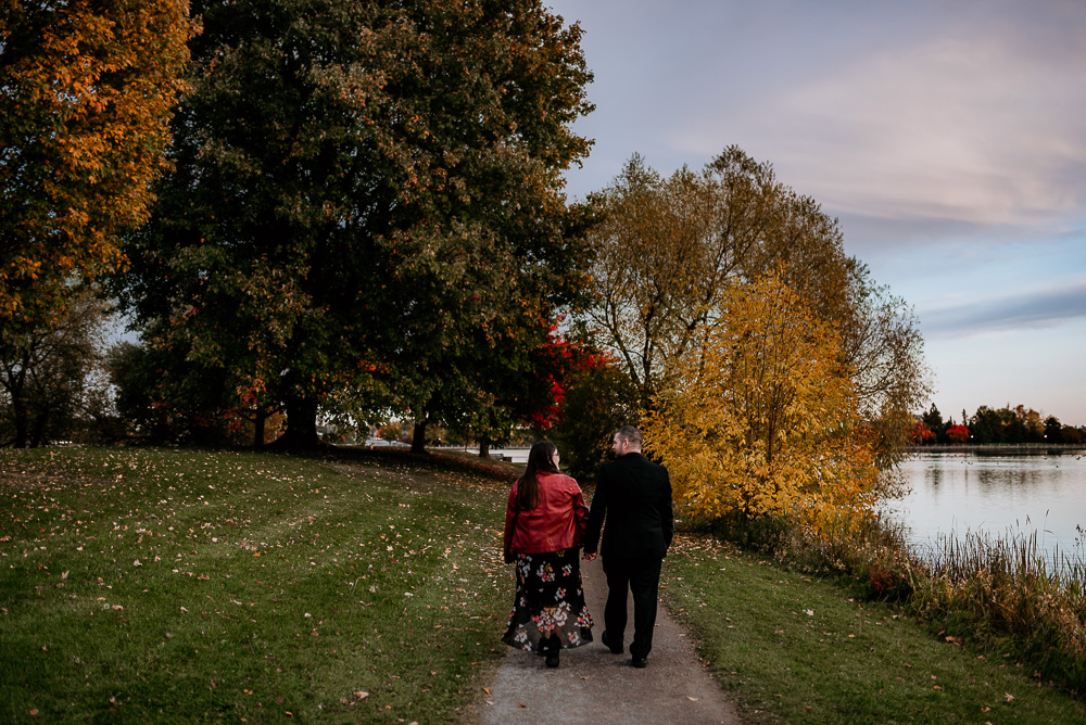 Couple take a stroll along Dow's Lake with the Arboretum and Carleton University in the distance. Bride looks up at her groom as she wears a beautiful red leather jacket.