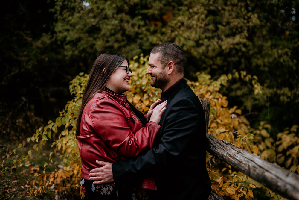 Newly engaged couple take on their engagement session at Ottawa's Dominion Arboretum and Dow's Lake. Soon to be bride is wearing a beautiful red leather jacket over a classic and beautiful black floral print dress. Photographed by Samantha Danis Photography.