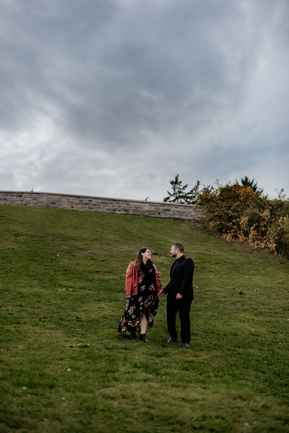 Newly engaged couple walking hand in hand down a hill at the Dominion Arboretum in Ottawa. Cloudy overcast skies create a dramatic effect while the brides red leather jacket pops against the green grass. Photo taken by Ottawa Photographer Samantha Danis.