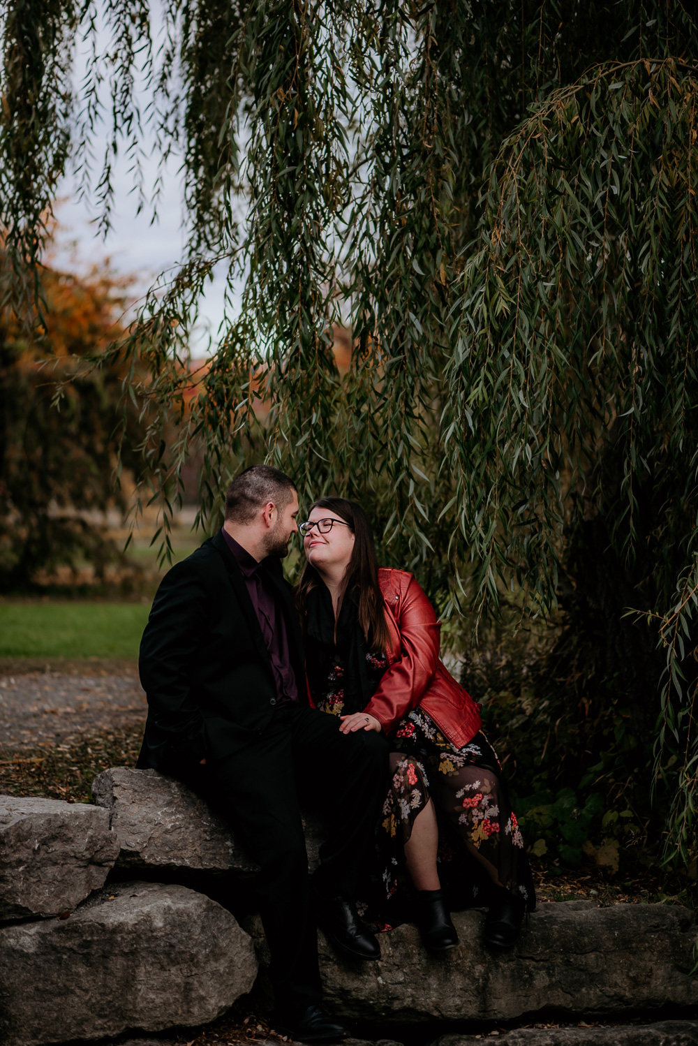 Engaged couple sitting on rocks under a willow tree. The bride leaning in to kiss her fiancé as she smiles. Photo taken by Ottawa engagement Photographer Samantha Danis.