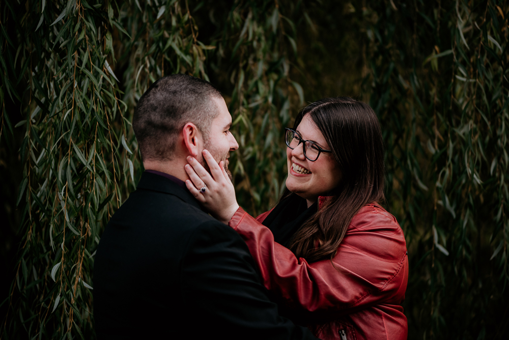 Fiancée holding her soon to be husband's face and lovingly gazing into his eyes. Engagement session at the Ottawa Dominion Arboretum captured by Samantha Danis Photography.