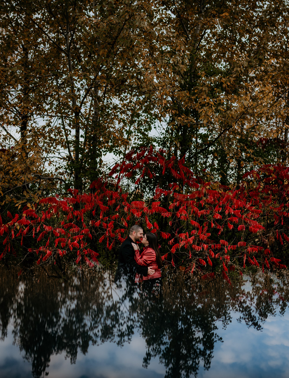 Couple standing in front of each other, holding each other in their arms as a red sumac tree glows behind them. A double exposure is created with an iPhone and reflects the sky underneath the couple creating the illusion of floating. Photo taken by Ottawa Wedding Photographer Samantha Danis.