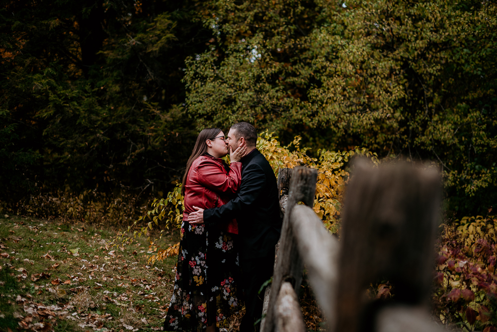 Engagement session at the Dominion Arboretum in Ottawa. Couple are leaning against a wooden fence while embracing. Ottawa Wedding Photographer Samantha Danis.