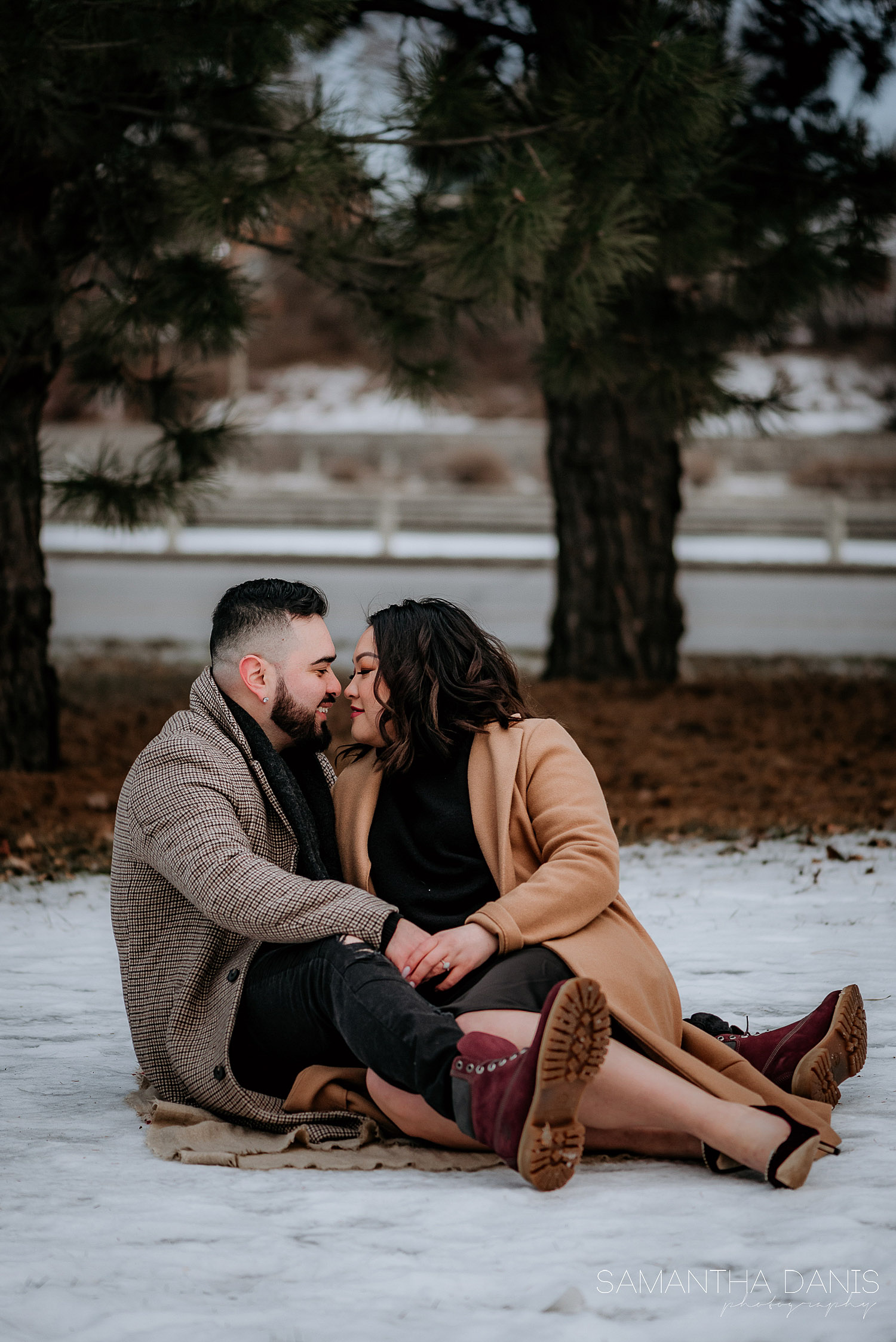 Engaged couple sitting in the snow at Lansdowne Park by the Rideau Canal. Framed by beautiful trees, the couple can be seen cuddling.