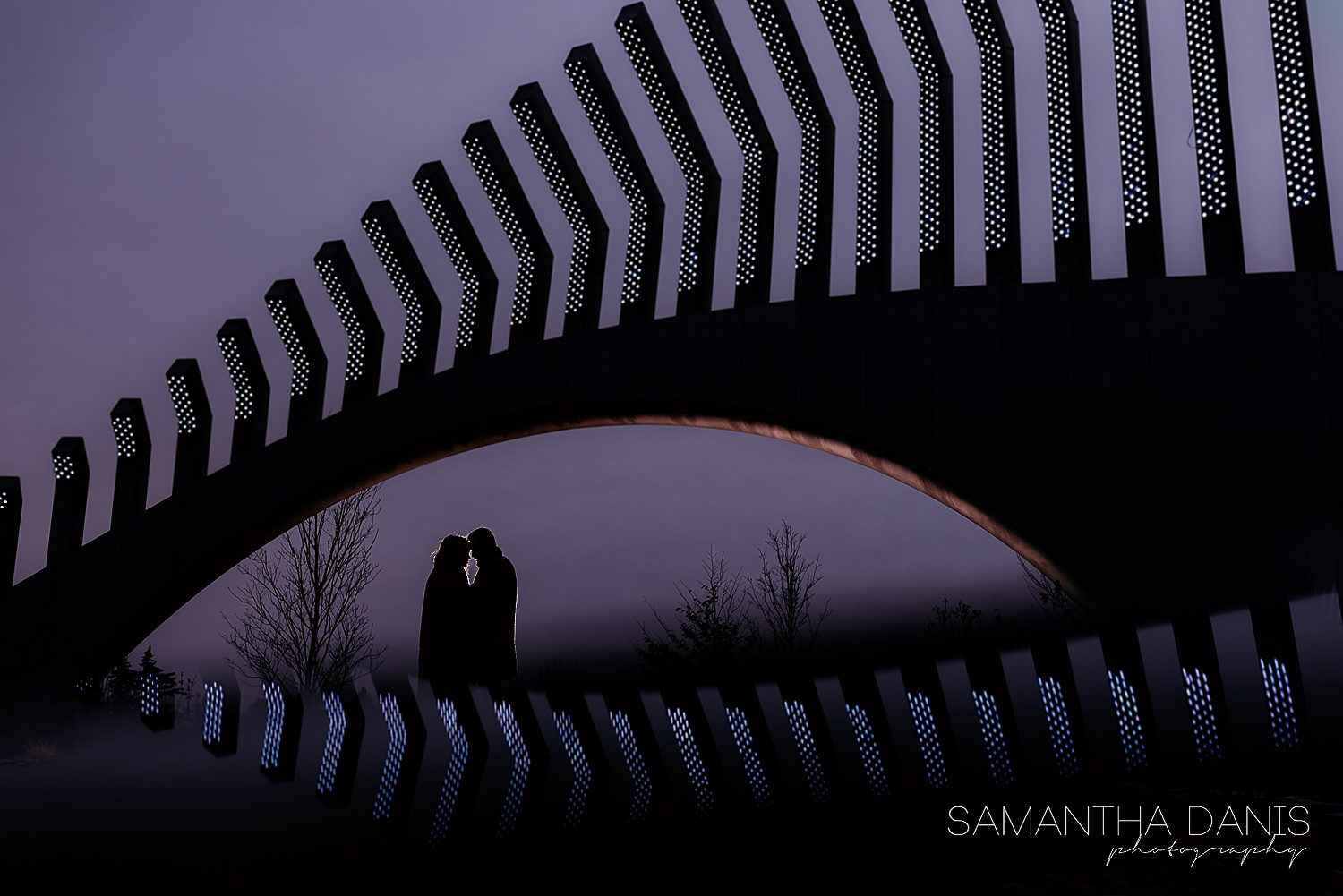 Couple standing under the TD Place Stadium sculpture and kissing. The beautiful purple sky enhances the silhouette of both the structure and the couple.