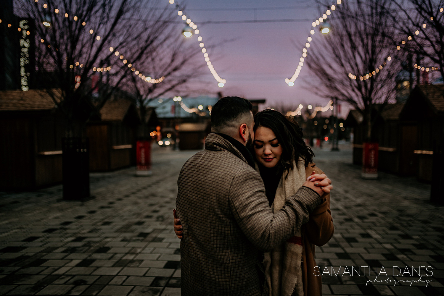 Engaged couple dancing hand in hand in the Lansdowne Courtyard. The setting sun creates a beautiful purple gradient in the sky which is accented by beautiful twinkle string lights.