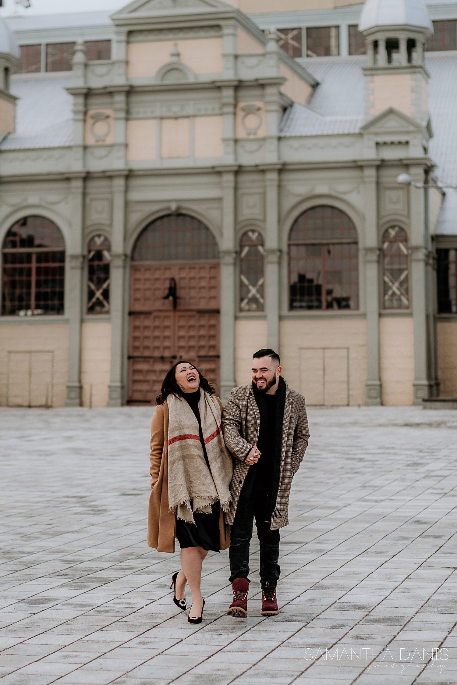 Engaged couple walking in front of Aberdeen Pavilion at Lansdowne Park Ottawa. Couple is laughing while walking arm in arm.