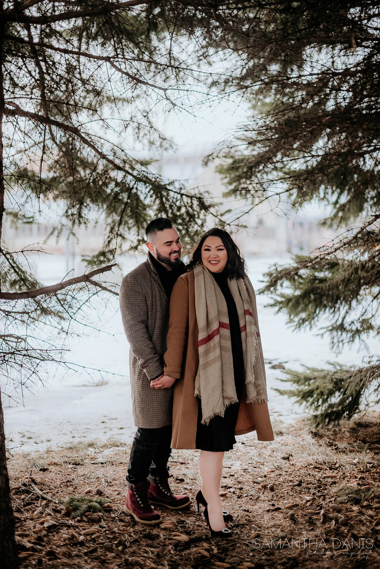 Couple holding hands and laughing under tree cover at Lansdowne Park. Groom looking at his fiancé while she looks at the camera and smiles.