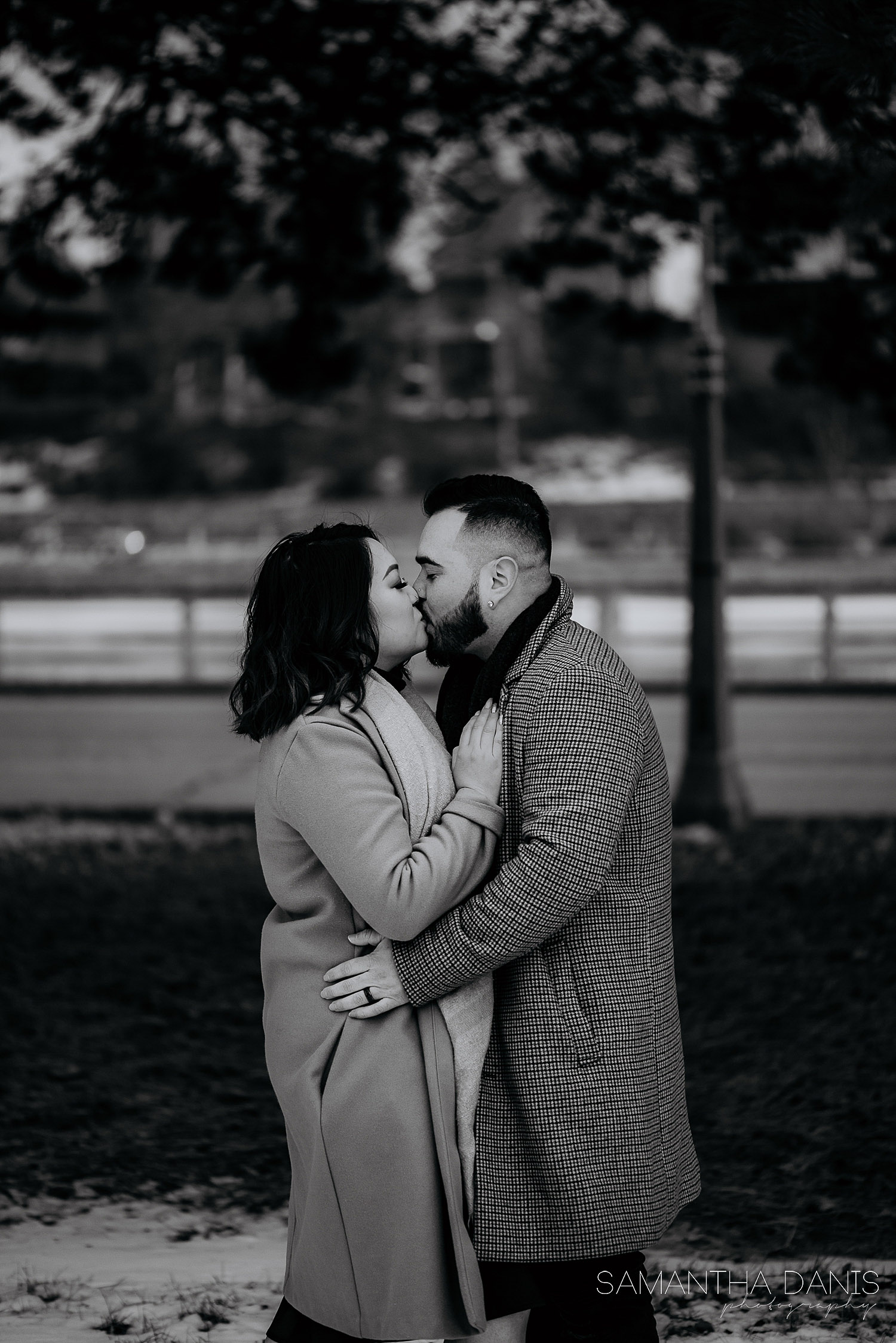 Bride and groom to be kissing in front of Rideau Canal. Black and white classic engagement photo.