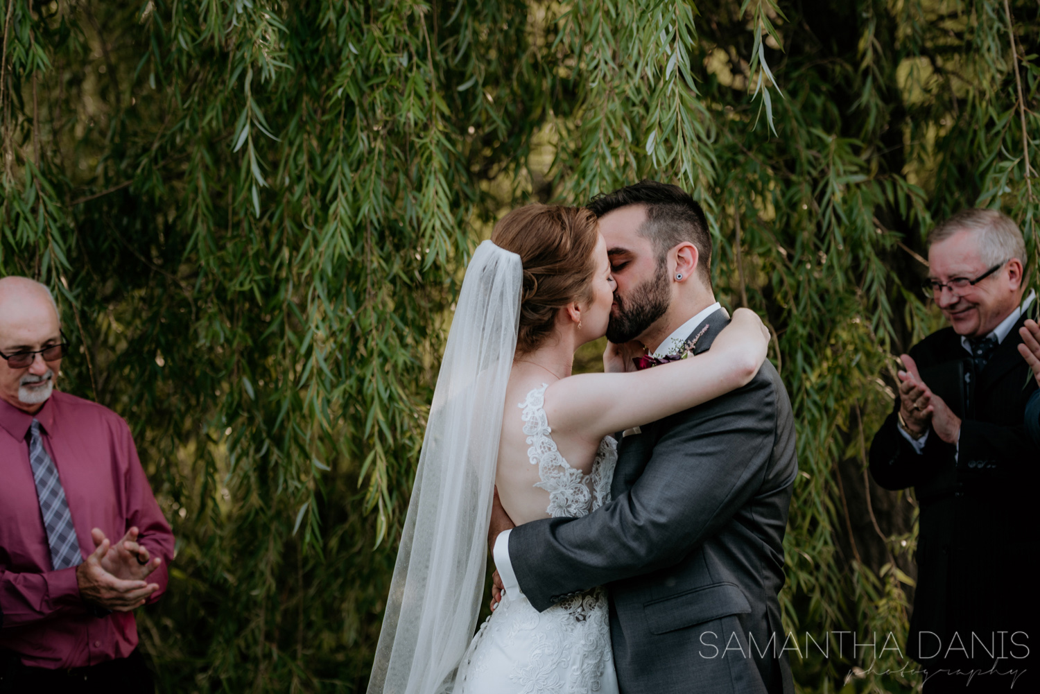 Ottawa Bride and Groom kiss for the first time after being pronounced husband and wife. Beautiful Gown by Stella York and Rings by Michael Hill.
