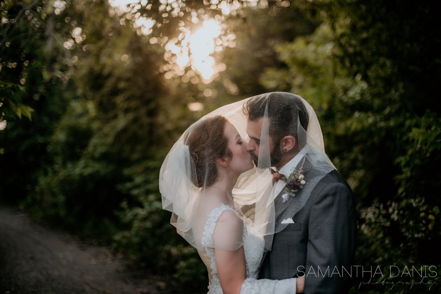 Sparkle veil covers both Ottawa Bride and Groom face to make for a dreamy romantic kiss shot under the setting sun. Ottawa Wedding Photographer.