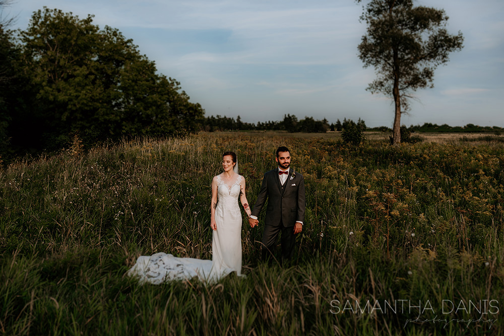 Bride and groom hold hands while looking in opposite direction. Background includes a beautiful field and tree at Kanata's Walter Baker Park. Ottawa Wedding Photographer.