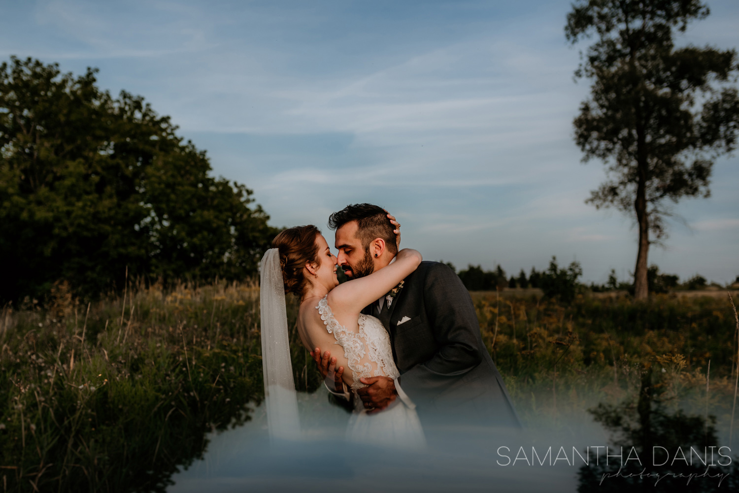Groom dip kisses his new wife in a field in Kanata, Ottawa. Sunset skin and blue skies for this Ottawa Couple.