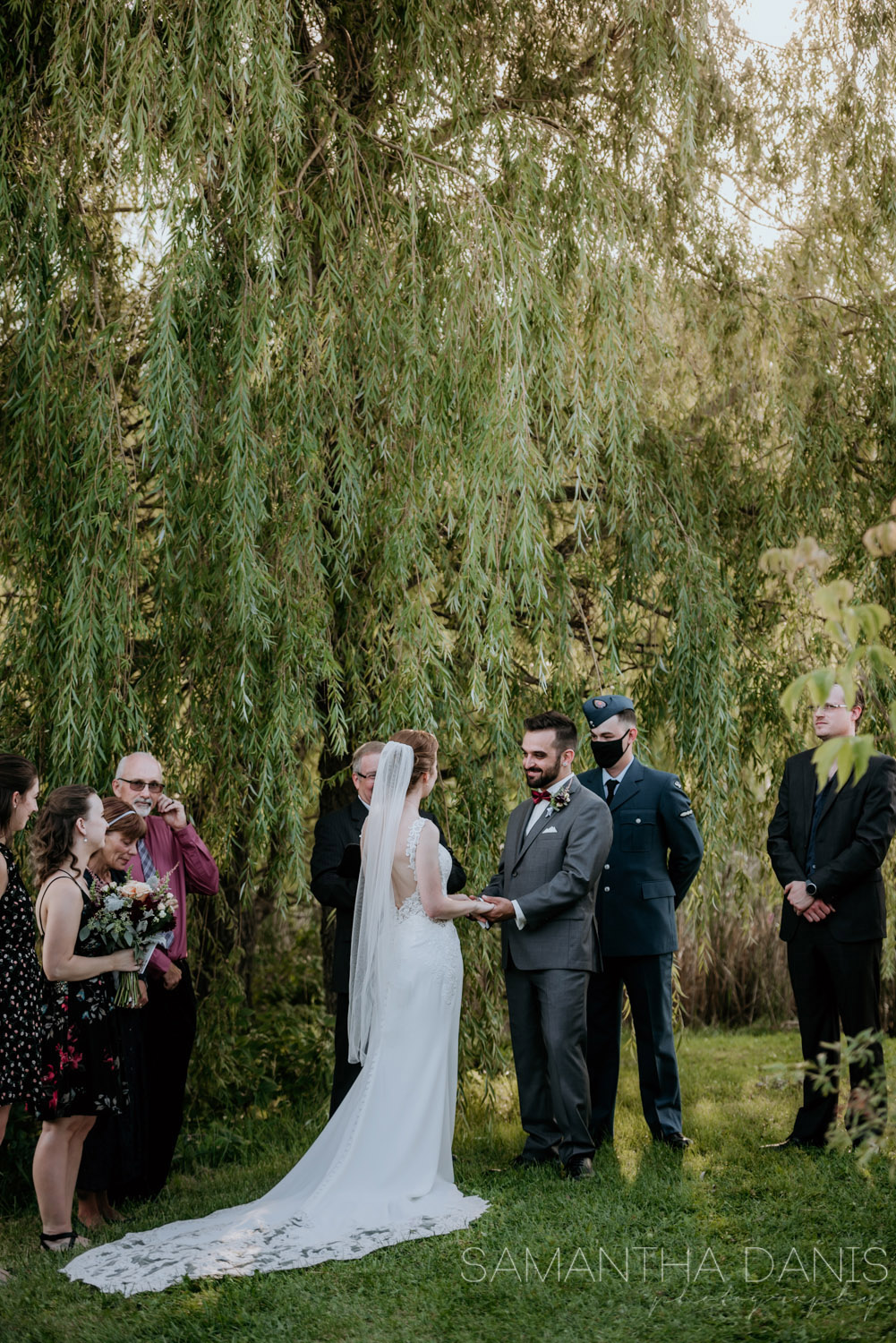 Sun shines through the willow tree as an Ottawa Bride and groom tell each other their vows during their elopement. Samantha Danis Photography